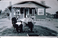 Two men and a baby in front of 2606 S. Garfield Avenue in August of 1920